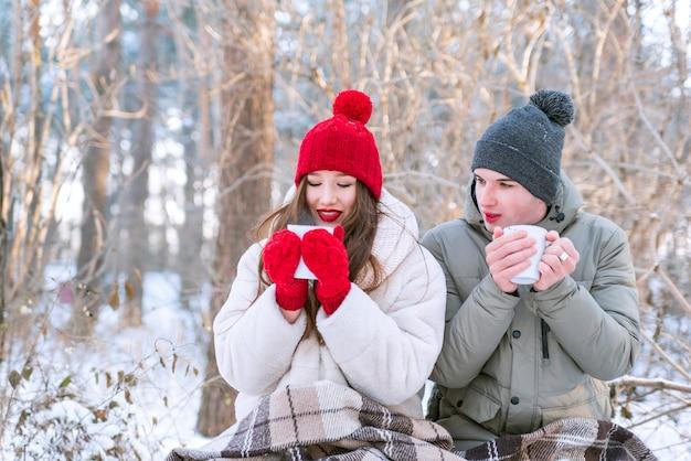 Зимой молодая пара устроила пикник в парке. влюбленные пьют чай в лесу.