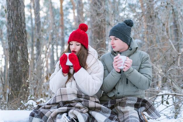 Молодая пара устроила пикник в зимнем лесу