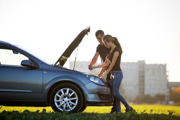 Молодая пара, красивый мужчина и привлекательная женщина в машине с выскочившим капотом, проверяя уровень масла в двигателе с помощью щупа на фоне ясного неба. транспорт, проблемы с транспортными средствами и концепция поломок.