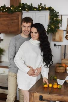 若いカップルのハンサムな男とかわいいモデルの女の子がクリスマスの朝に飾られたキッチンでポーズをとる
