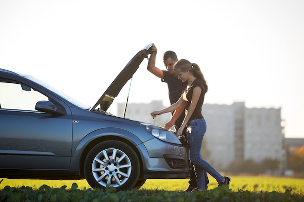 Young couple, handsome man and attractive woman at car with popped hood checking oil level in engine using dipstick on clear sky. transportation, vehicles problems and breakdowns concept.
