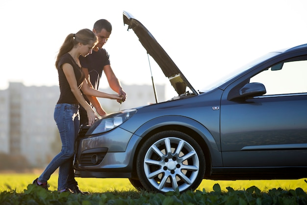 Young couple, handsome man and attractive woman at car with popped hood checking oil level in engine using dipstick on clear sky