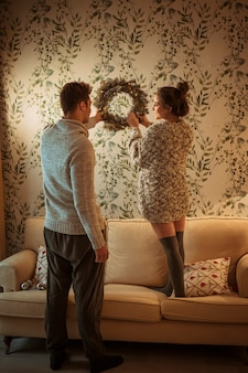 Young couple hanging Christmas wreath on light wall