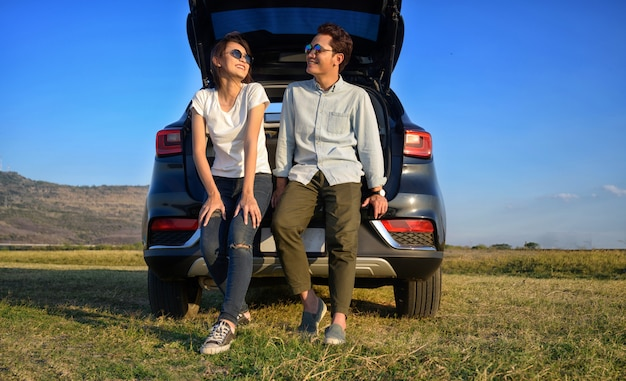 Young couple happy asian out on a road trip. asian couple man  and woman sitting on back of car travel to mountain and lake in holiday with car road trip