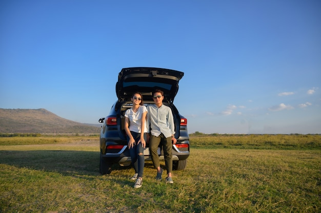Young couple happy asian out on a road trip.