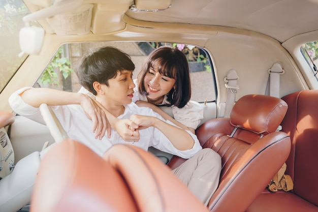 Young couple happy in car on road trip. love, wedding and valentine concept.