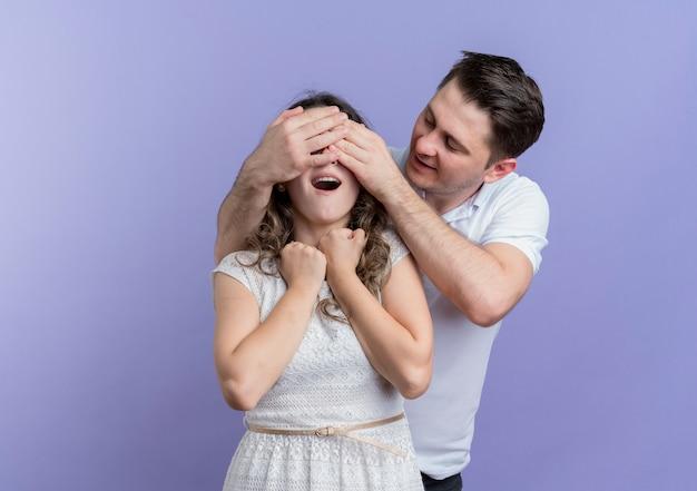 青に驚きを作る彼女のガールフレンドの目を閉じている若いカップルの幸せな男