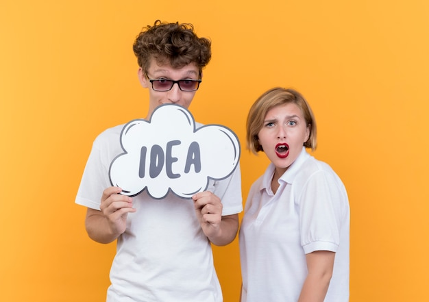 그의 여자 친구가 오렌지 벽 위에 서 혼란 스 러 워하는 동안 단어 아이디어와 연설 거품 기호를 들고 젊은 부부 행복 한 사람