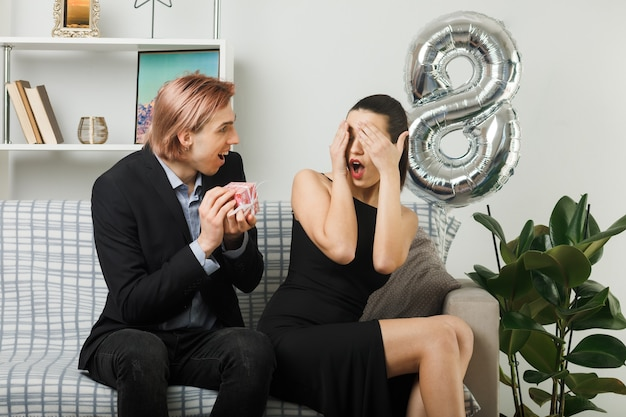 Young couple on happy women day excited guy gives present to surprised girl covered eyes with hands sitting on sofa in living room