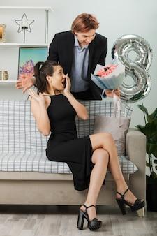 Giovane coppia in felice giornata delle donne ragazzo con bouquet in piedi dietro al divano con una ragazza in soggiorno