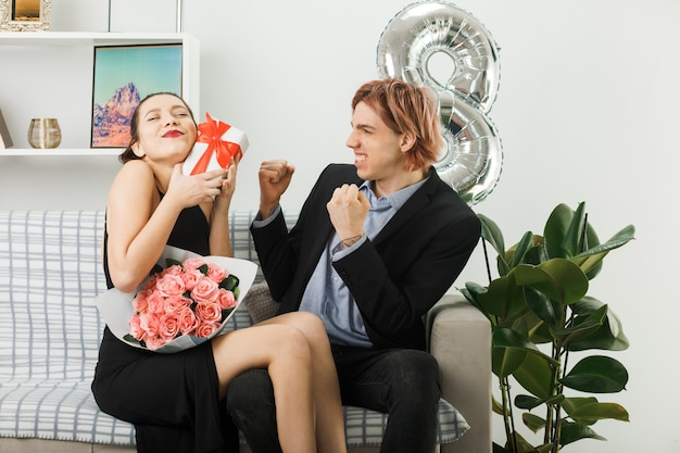 Young couple on happy women day holding present with bouquet guy showing yes gesture sitting on sofa in living room