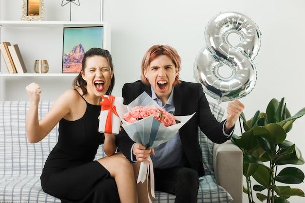 Giovane coppia in una felice giornata della donna che tiene un regalo con un bouquet seduto sul divano in soggiorno