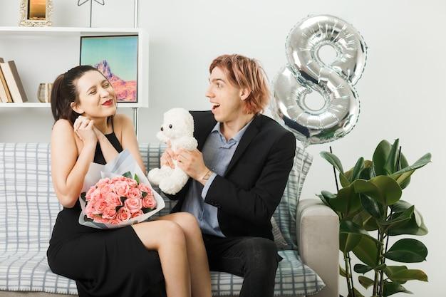 Giovane coppia in felice giornata delle donne che tiene orsacchiotto con bouquet seduto sul divano in soggiorno