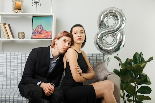Young couple on happy women day sad guy putting head on strict girl shoulder sitting on sofa in living room