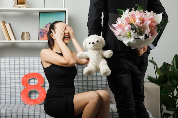 Young couple on happy women day smiling covered eyes with hands girl sitting on sofa guy holding teddy bear with bouquet on waist in living room