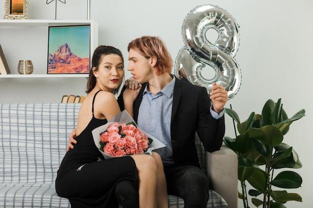 Coppia giovane in felice giornata della donna con bouquet seduto sul divano in soggiorno