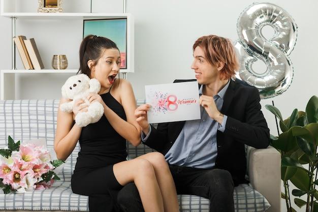 Coppia giovane in felice giornata della donna con orsacchiotto e cartolina seduti sul divano in soggiorno