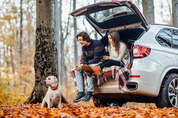 若いカップルは森の中の自動車の近くで犬と一緒にピクニックをします。