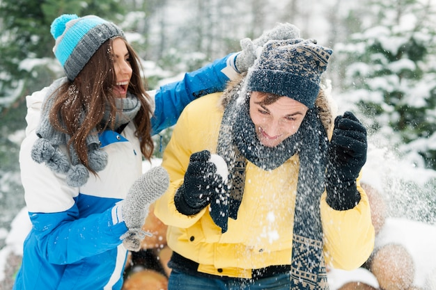 Young couple have fun during the snowball fight