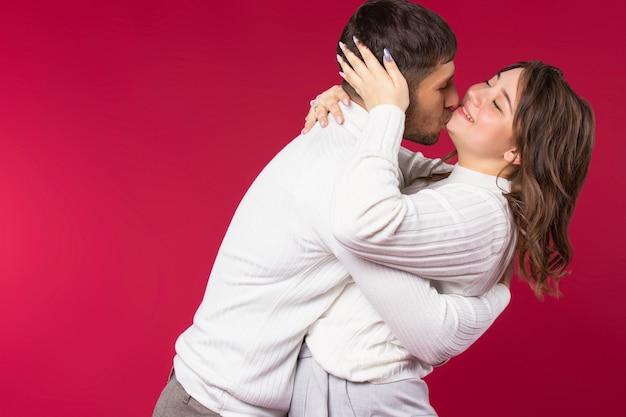 Молодая пара весело обнимается и дурачится на красном фоне с пустым боковым пространством.