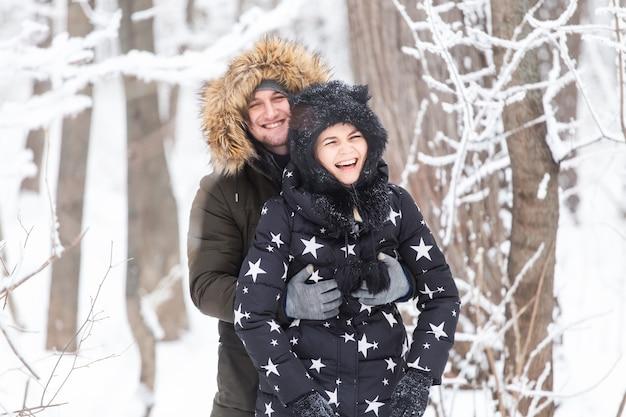 Молодая пара развлекается в заснеженном парке. зимний сезон.