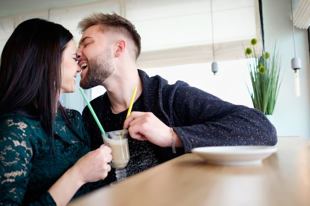 Young couple have fun sitting in cafe and drinking capuccino, man bites girl's nose in joke manner, both laughing