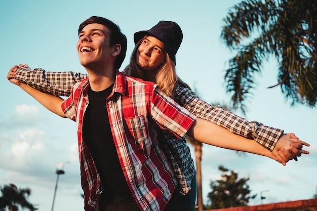 若いカップルは一緒に楽しんでいます、彼女は彼女のボーイフレンドに戻って登ります