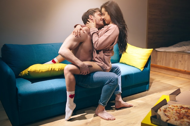 Young couple have intimacy in kitchen in night. passionate shirtless man sit on sofa and kiss sensual woman.