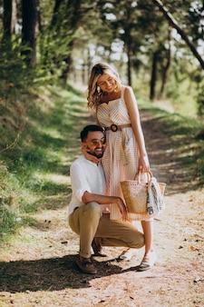森の中で散歩を持っている若いカップル