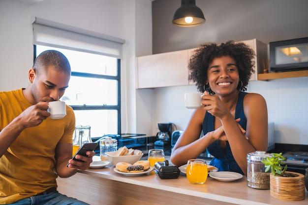 自宅で朝食を持っている若いカップル。