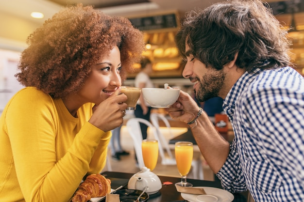 Young couple having a breakfast at cafe, drinking a tea and coffee looking at each other