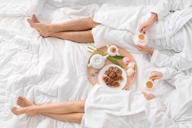 Молодая пара завтракает в постели у себя дома