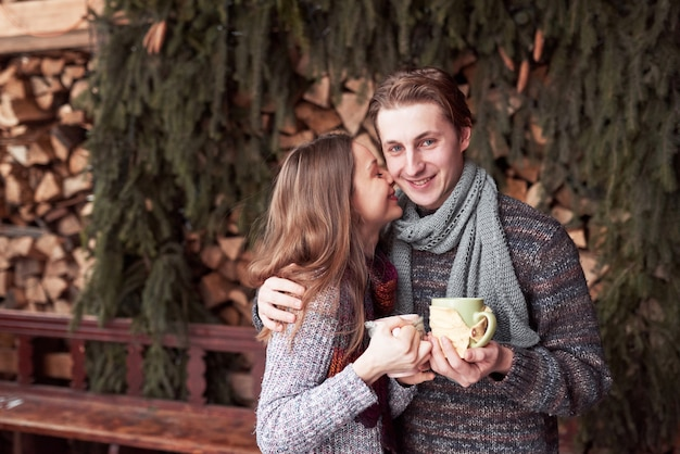 Young couple having breakfast in a romantic cabin outdoors in winter. winter holiday and vacation. christmas couple of happy man and woman drink hot wine. couple in love