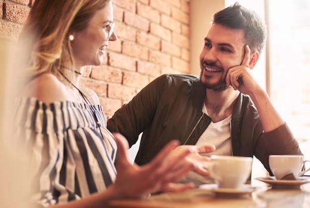 Молодая пара разговаривает за чашкой кофе