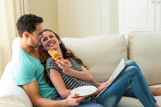 Young couple having croissant while reading newspaper in living room
