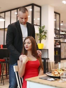 レストランで夕食を持っている若いカップル