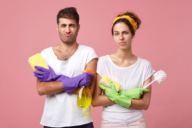 Young couple having frowning faces keeping their hands crossed holding brush, detergent and mops wearing protective gloves and white casual t-shirts having bad mood and unwillingness to clean house
