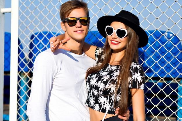 Молодая пара весело в летнее время, объятия, эмоции, в стильной черно-белой одежде и солнцезащитных очках