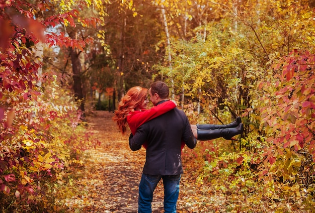 Young couple having fun in autumn forest. man holds his woman in his arms and dances