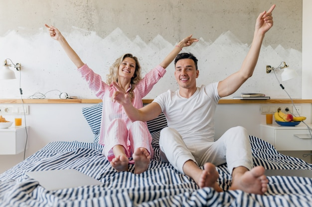 Young couple having fun on bed in morning, smiling happy, family living together