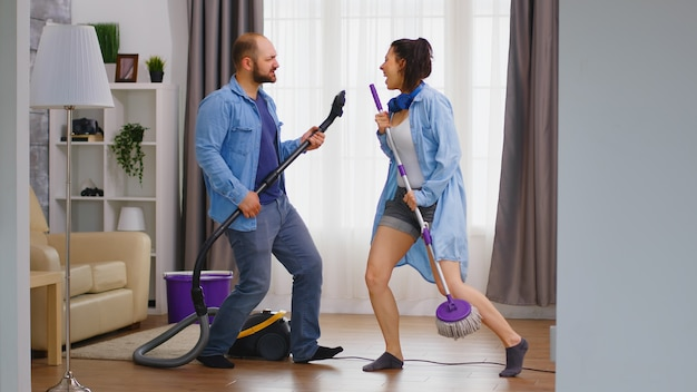 掃除機とモップを楽器として使ってハウスキーピングを楽しんでいる若いカップル。