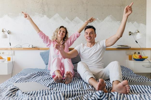 朝のベッドで楽しんで、幸せな笑顔の家族が一緒に住んでいる若いカップル