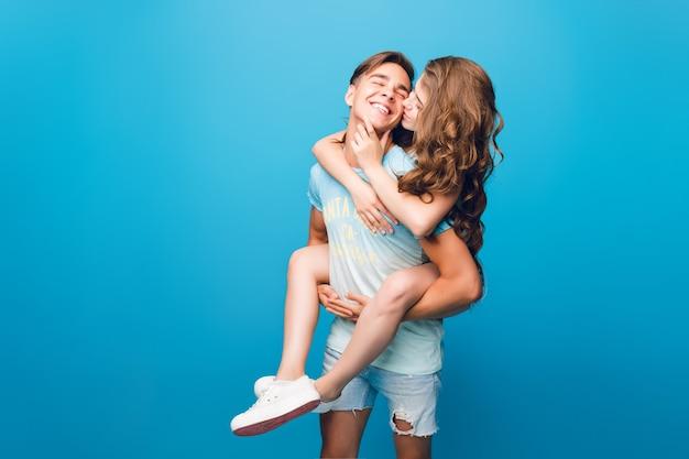 スタジオで青色の背景に楽しんで若いカップル。長い巻き毛のかわいい女の子がハンサムな男の後ろに乗っています。彼女は彼にキスをしています。