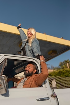 Молодая пара веселится в автомобильной поездке с женщиной в заднем багажнике