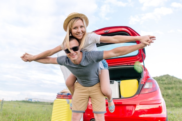 Young couple having fun outdoors riding each other in front of the car with things for camping