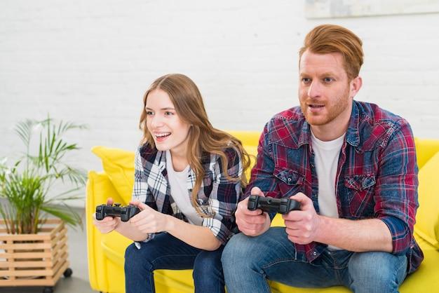 Молодая пара весело играет в видеоигры у себя дома