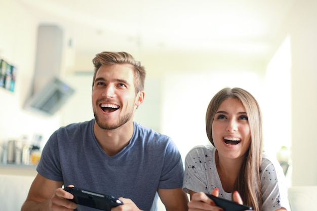 Young couple having fun playing videogame at home
