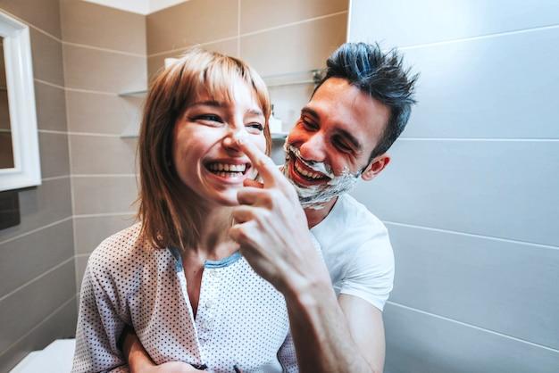 Молодая пара весело играет с пеной для бритья в ванной комнате