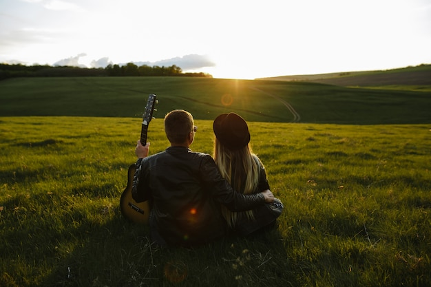 Young couple having fun at a sunset under the guitar song