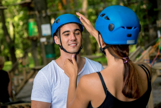 Young couple having fun time in adventure rope park. climbing equipment. wearing safety belt and protective helmets.